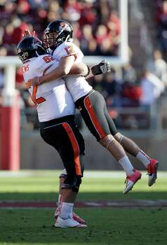 Oregon State kicker Trevor Romaine (12) and offensive linesman Gavin Andrews (62) against Stanford during the second half of an NCAA college football game in Stanford, Calif., Saturday, Nov. 10, 2012. (AP Photo/Jeff Chiu) Photo: Jeff Chiu, Associated Press / AP