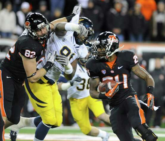 Oregon State Colby Prince (82) blocks for Storm Woods (24) against California's Deandre Coleman (91) during the first half of an NCAA college football game in Corvallis, Ore., Saturday Nov.,17, 2012. (AP Photo/Greg Wahl-Stephens) Photo: Greg Wahl-Stephens, Associated Press / FR29287 AP