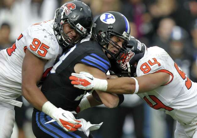 Brigham Young quarterback Riley Nelson, center, is sacked by Oregon State defensive ends Scott Crichton (95) and  Devon Kell (94) during the second half of an NCAA college football game Saturday, Oct. 13, 2012, in Provo, Utah. Oregon State defeated BYU 42-24. (AP Photo/Rick Bowmer) Photo: Rick Bowmer, Associated Press / AP