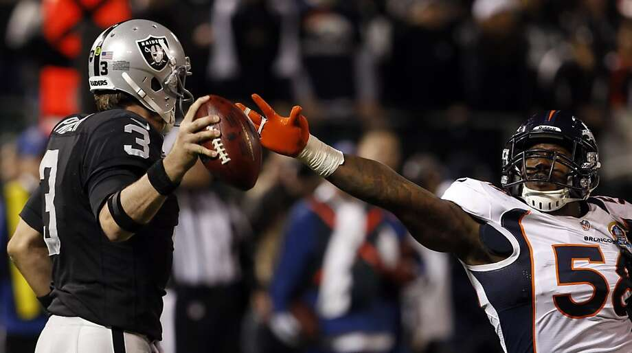 Von Miller, right, puts a little pressure on Carson Palmer in the fthird quarter. The Oakland Raiders played the Denver Broncos at O.co Coliseum in Oakland, Calif., on Thursday, December 6, 2012. Photo: Carlos Avila Gonzalez, The Chronicle