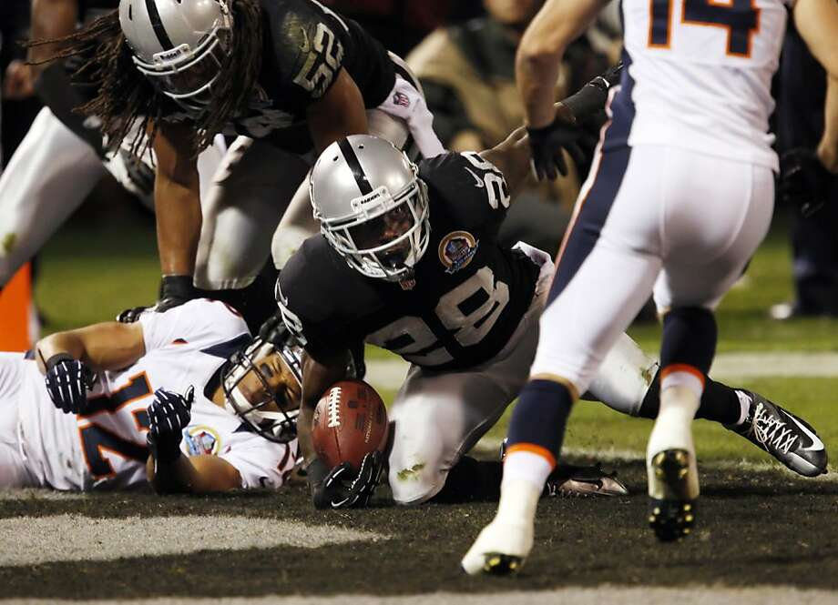Phillip Adams rolls into the end zone after intercepting a pass from Peyton Manning intended for Matthew Willis in the second quarter. The Oakland Raiders played the Denver Broncos at O.co Coliseum in Oakland, Calif., on Thursday, December 6, 2012. Photo: Carlos Avila Gonzalez, The Chronicle