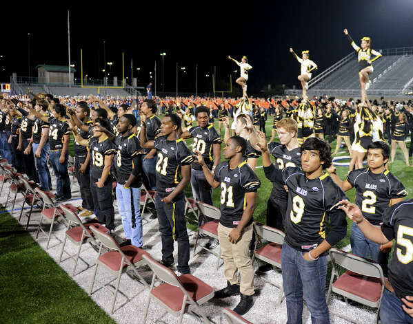 Brennan varsity football players stand for their Alma Mater during a NISD three school football playoff pep rally for Brandeis, Brennan and O'Connor at Farris Stadium in San Antonio, Thursday, December 6, 2012.