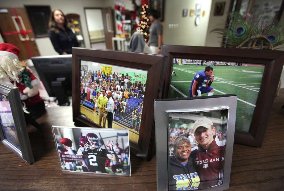Tivy High School office workers circulate around receptionist Bessie Fifer's desk where she has placed photos of football hero, graduate, and Heisman Trophy candidate Johnny Maziel, in Kerrville, Tx. Wednesday, Dec. 5, 2012. Photo: Bob Owen, San Antonio Express-News / © 2012 San Antonio Express-News