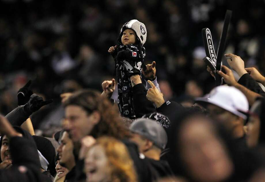 A Raiders fan brought his child to the game and held him up in the fourth quarter of play during a timeout. The Oakland Raiders played the Denver Broncos at O.co Coliseum in Oakland, Calif., on Thursday, December 6, 2012. Photo: Carlos Avila Gonzalez, The Chronicle