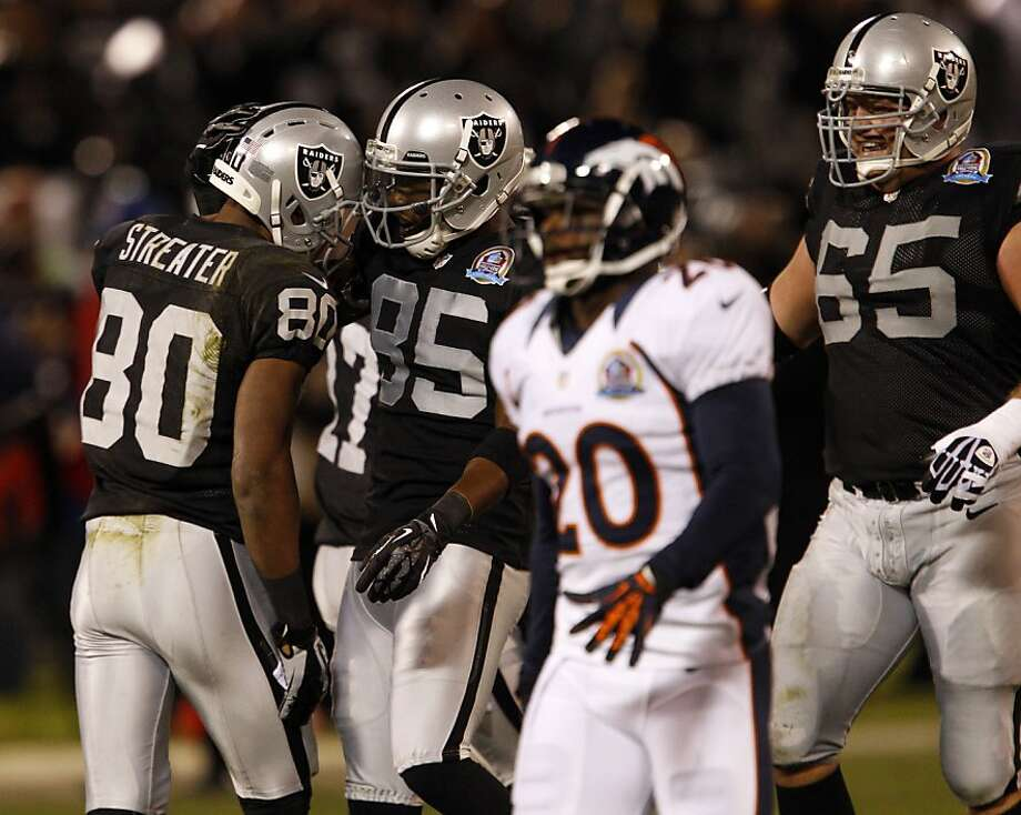 Rod Streater, left, is congratulated on his reception for a 58-yard gain in the first quarter by Darrius Heyward-Bey, center. The Oakland Raiders played the Denver Broncos at O.co Coliseum in Oakland, Calif., on Thursday, December 6, 2012. Photo: Carlos Avila Gonzalez, The Chronicle