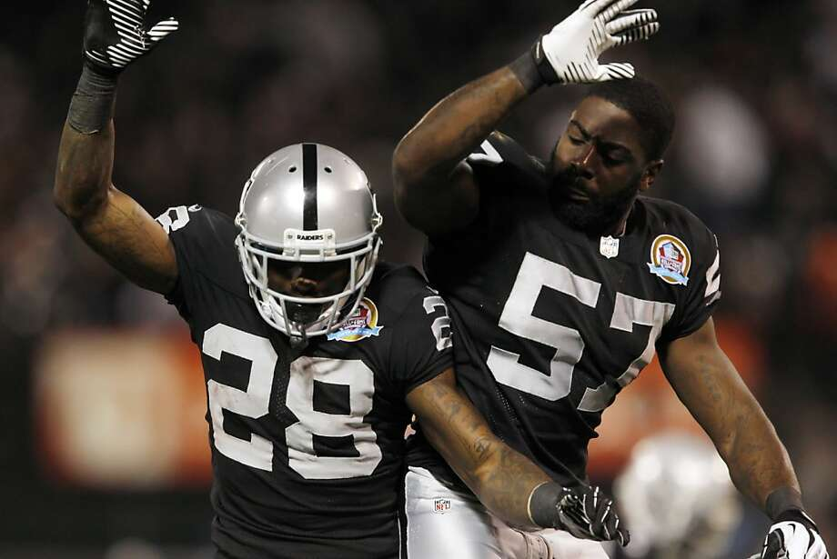 Phillip Adams, left, and Keenan Clayton, right, celebrate Adams's second quarter interception. The Oakland Raiders played the Denver Broncos at O.co Coliseum in Oakland, Calif., on Thursday, December 6, 2012. Photo: Carlos Avila Gonzalez, The Chronicle