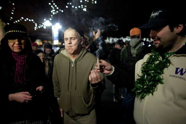 "John, center, passes around a joint on Thursday, December 6, 2012 during a ""stash mob"" at Seattle's International Fountain. Recreational use of marijuana was legalized by voters in Washington State and people have been celebrating by smoking publicly. Photo: JOSHUA TRUJILLO / SEATTLEPI.COM"