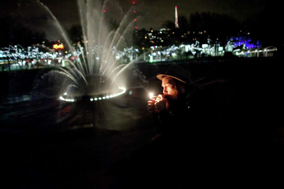 "A man lights a joint at the International Fountain on Thursday, December 6, 2012 during a ""stash mob"" at Seattle's International Fountain. Recreational use of marijuana was legalized by voters in Washington State and people have been celebrating by smoking publicly. Photo: JOSHUA TRUJILLO / SEATTLEPI.COM"