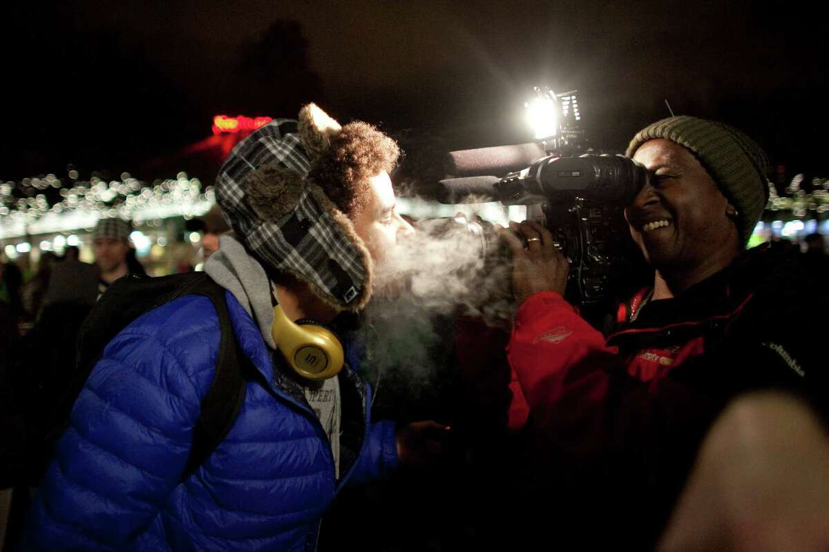 Marshall Mung blows marijuana smoke into the lens of KIRO/7 photographer Frank Metz's camera on Thursday, December 6, 2012 during a