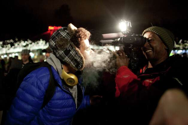 "Marshall Mung blows marijuana smoke into the lens of KIRO/7 photographer Frank Metz's camera on Thursday, December 6, 2012 during a ""stash mob"" at Seattle's International Fountain. Recreational use of marijuana was legalized by voters in Washington State and people have been celebrating by smoking publicly. Photo: JOSHUA TRUJILLO / SEATTLEPI.COM"