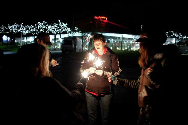 "Penny Graves, center, holds sparklers with others smoking marijuana on Thursday, December 6, 2012 during a ""stash mob"" at Seattle's International Fountain. Recreational use of marijuana was legalized by voters in Washington State and people have been celebrating by smoking publicly. Photo: JOSHUA TRUJILLO / SEATTLEPI.COM"