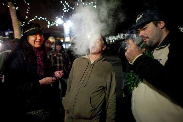 "John, center, blows smoke on Thursday, December 6, 2012 during a ""stash mob"" at Seattle's International Fountain. Recreational use of marijuana was legalized by voters in Washington State and people have been celebrating by smoking publicly. Photo: JOSHUA TRUJILLO / SEATTLEPI.COM"