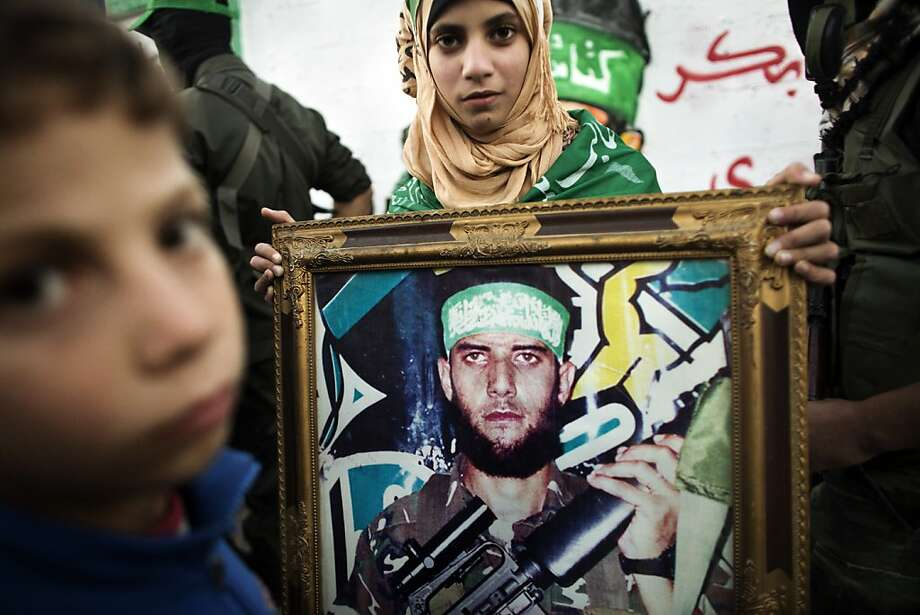 A Palestinian woman holds the portrait of a killed relative belonging to the Ezzedine al-Qassam brigade during a march by Hamas armed wing in Beit Hanun on December 6, 2012. The Hamas government confirmed that the Islamist movement's exiled politburo chief Khaled Meshaal was due in the Gaza Strip to celebrate its 25th anniversary. Photo: Marco Longari, AFP/Getty Images