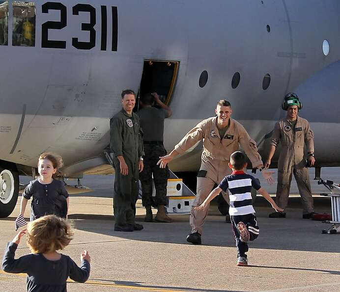 Children sprint towards the C-130 to meet their dads as members of the US Marines return from their