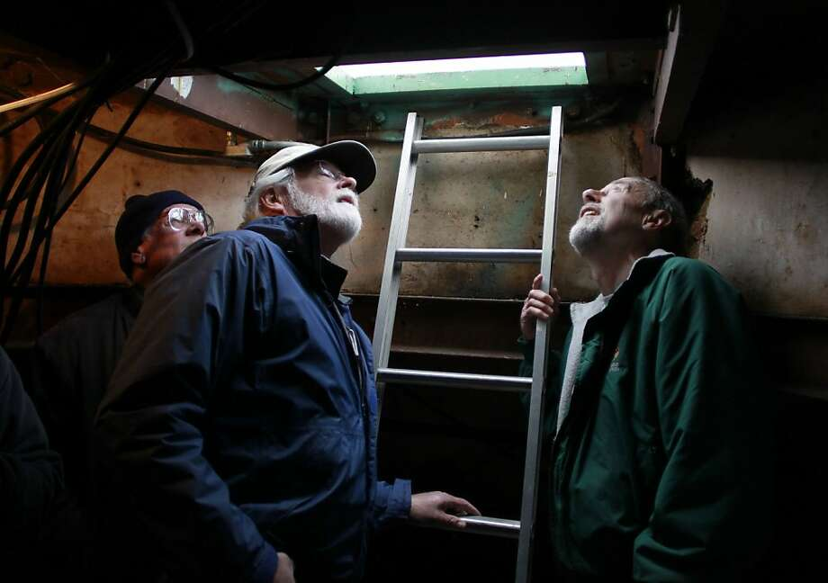 Jerry Farley (left), John Gallagher (center) and Dick Heron catch a glimpse of the historic beacon through a small access hatch on the summit of Mount Diablo on Thursday, Nov. 29, 2012. Volunteers are preparing for the annual beacon lighting ceremony on Dec. 7. Photo: Paul Chinn, The Chronicle