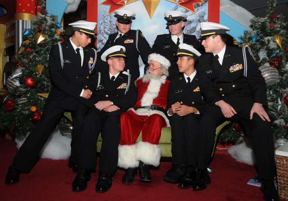 Santa Claus sits with Brewster High school's Junior Navy ROTC members at the Danbury Fair Mall on Thursday Dec. 3,2009. Front row from left, Ariel Rosero,17, Kyle Bond,17, Santa Claus, Jonathan Ho,17, Thomas Columbo,17, back row left, Jason Kaplan,17 and back row right, Chris Coleman, 17. Photo: Lisa Weir / The News-Times
