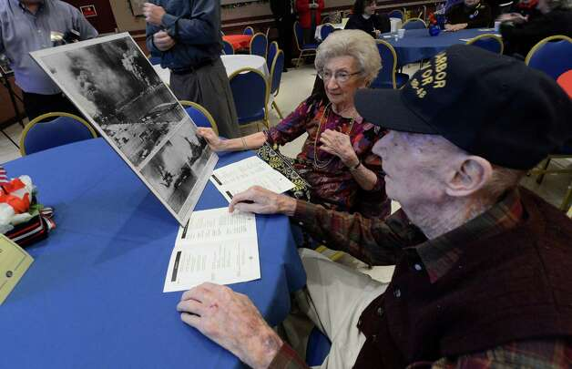 Pearl Harbor survivor Bill Langston, right, looks over newspaper clippings of the Pearl Harbor raid with his wife, Jean, at the Pearl Harbor Day Memorial Observance at the J.E. Zaloga Post in Albany, N.Y., on Dec. 7, 2012. It is the 71st anniversary of the bombing of Pearl Harbor.  (Skip Dickstein/Times Union) Photo: SKIP DICKSTEIN / 00020374A