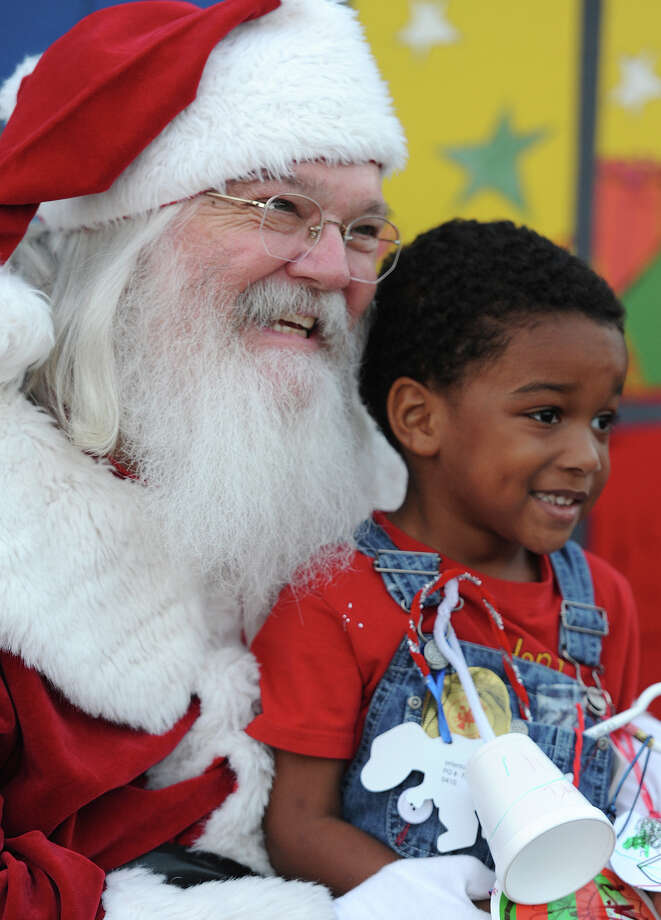 Dakari Keller, 3, poses with Santa for a photo during a Christmas event at the Art Museum of Southeast Texas on Thursday.  Photo taken Thursday, December 06, 2012 Guiseppe Barranco/The Enterprise Photo: Guiseppe Barranco, STAFF PHOTOGRAPHER / The Beaumont Enterprise