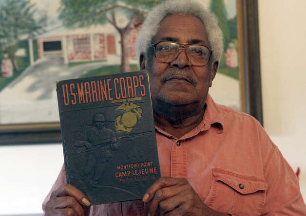 Veteran Calvin Curtis holds a book about Marines at Montford Point at Camp Lejeune where he trained during World War II. Photo: John Davenport, San Antonio Express-News / ©San Antonio Express-News/Photo Can Be Sold to the Public