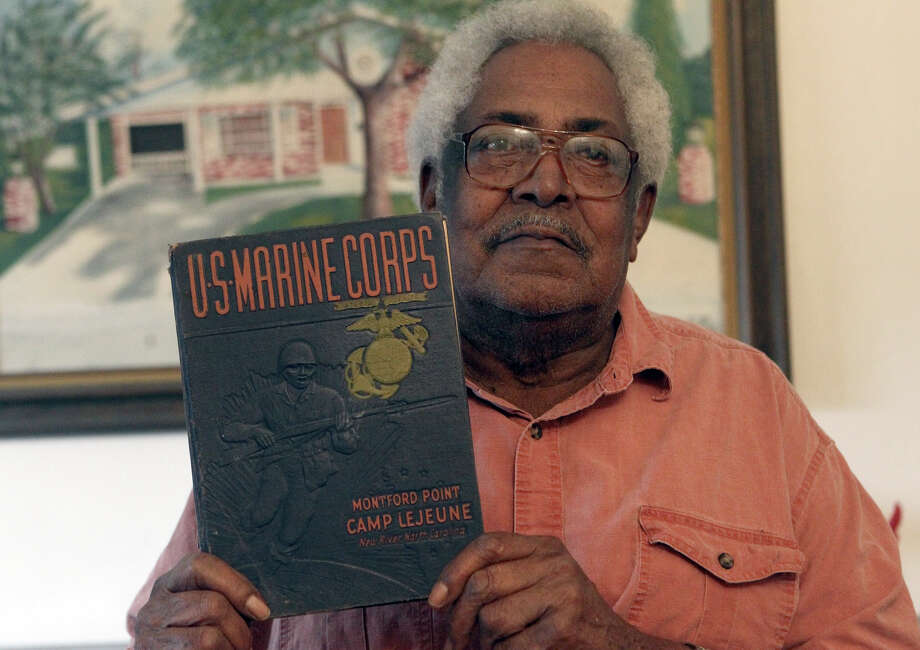 Marine Corps veteran Calvin Curtis holds a book about Montford Point at Camp Lejeune where he trained with other African Americans during World War II. Today, Curtis will receive a replica of the Congressional Gold Medal for his service. Photo: John Davenport, San Antonio Express-News / ©San Antonio Express-News/Photo Can Be Sold to the Public