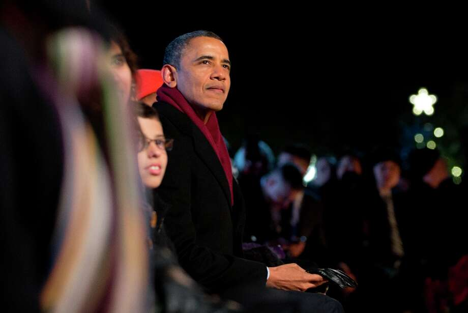 President Barack Obama looks to the stage during the annual National Christmas Tree Lighting on the Ellipse, Thursday, Dec. 6, 2012, in Washington. This year's giant blue spruce is new, transplanted in October on the Ellipse, south of the White House.  (Carolyn Kaster / AP Photo) Photo: Carolyn Kaster, Associated Press / AP