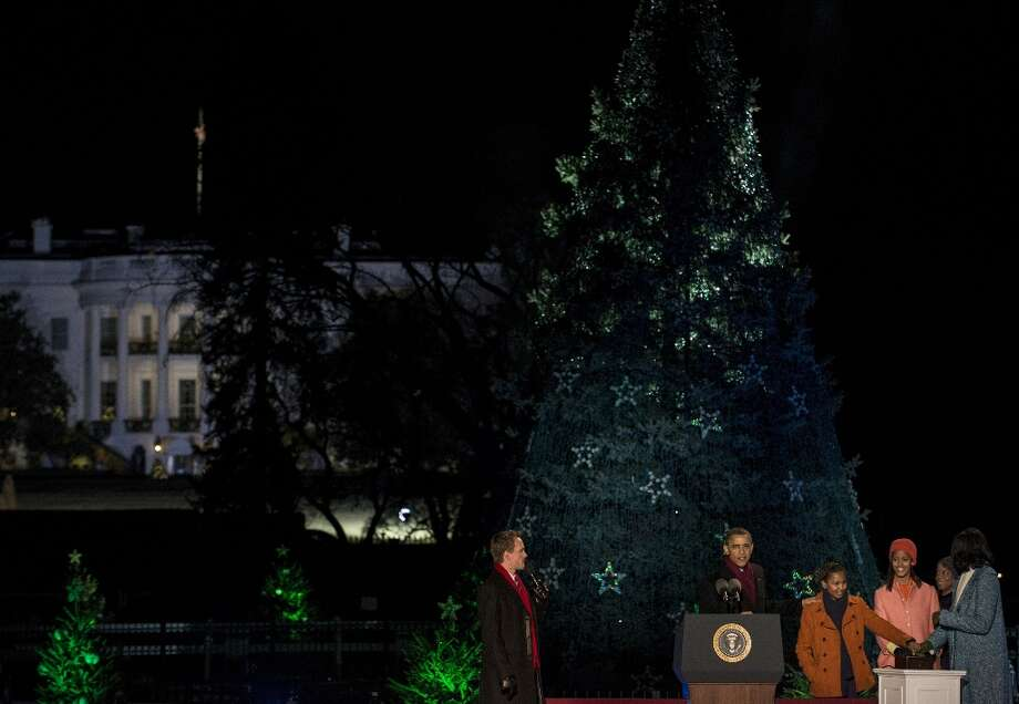 Actor Neil Patrick Harris (L) watches as US President Barack Obama, US First Lady Michelle Obama and their children Sasha and Malia illuminate the National Christmas Tree during the 90th annual lighting on the Ellipse of the National Mall December 6, 2012 in Washington, DC. Obama and others attended the event which included entertainment before the lighting of the National Christmas Tree.  (Brendan Smialowski / Getty Images) Photo: BRENDAN SMIALOWSKI, AFP/Getty Images / 2012 Brendan Smialowski