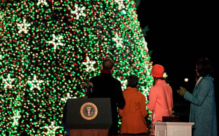US President Barack Obama, Sasha Obama, Malia Obama and US First Lady Michelle Obama look at the National Christmas Tree during the 90th annual National Christmas Tree Lighting on the Ellipse of the National Mall December 6, 2012 in Washington, DC. Obama and others attended the event which included entertainment before the lighting of the National Christmas Tree.  (Brendan Smialowski / Getty Images) Photo: BRENDAN SMIALOWSKI, AFP/Getty Images / 2012 Brendan Smialowski