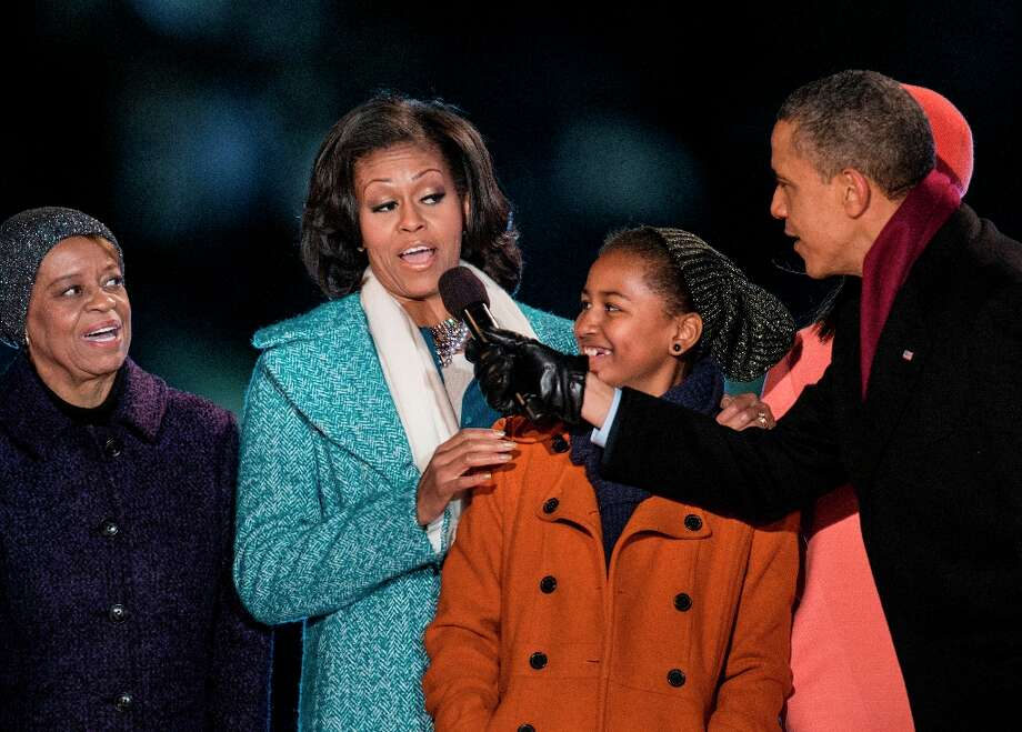 Marian Robinson (L) and Sasha Obama (2R) watch as US President Barack Obama points a microphone toward US first lady Michelle Obama while singing Santa Clause is Coming to Town during the 90th annual National Christmas Tree Lighting on the Ellipse of the National Mall December 6, 2012 in Washington, DC. Obama and others attended the event which included entertainment before the lighting of the National Christmas Tree.  (Brendan Smialowski / Getty Images) Photo: BRENDAN SMIALOWSKI, AFP/Getty Images / 2012 Brendan Smialowski