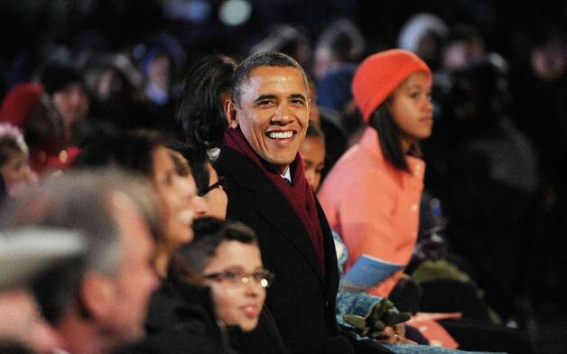 U.S. President Barack Obama with his wife Michelle Obama and their daughters Malia and Sasha Obama enjoying the concert during the 90th National Christmas Tree Lighting Ceremony on the Ellipse behind the White House on December 6, 2012 in Washington, DC. This year is the 90th annual National Christmas Tree Lighting Ceremony. Photo: Pool, Getty Images / 2012 Getty Images