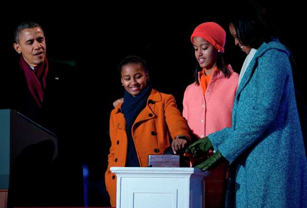 President Barack Obama, first lady Michelle Obama and their daughters Sasha and Malia flip the switch to light the National Christmas Tree during the annual National Christmas Tree Lighting on the Ellipse, Thursday, Dec. 6, 2012, in Washington. This year's giant blue spruce is new, transplanted in October on the Ellipse, south of the White House. (Carolyn Kaster / AP Photo) Photo: Carolyn Kaster, Associated Press / AP
