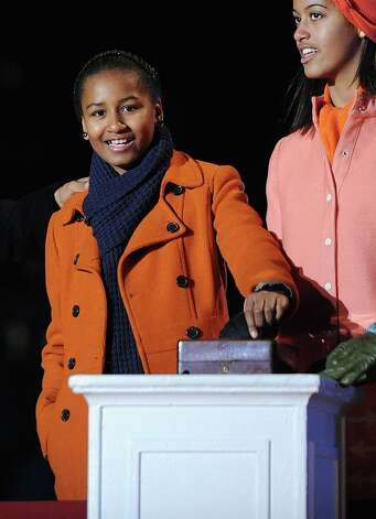Sasha Obama, left, and her sister, Malia, light the 90th National Christmas Tree during the Lighting Ceremony on the Ellipse behind the White House in Washington, D.C., on Thursday, December 6, 2012. Photo: Olivier Douliery, McClatchy-Tribune News Service / Abaca Press