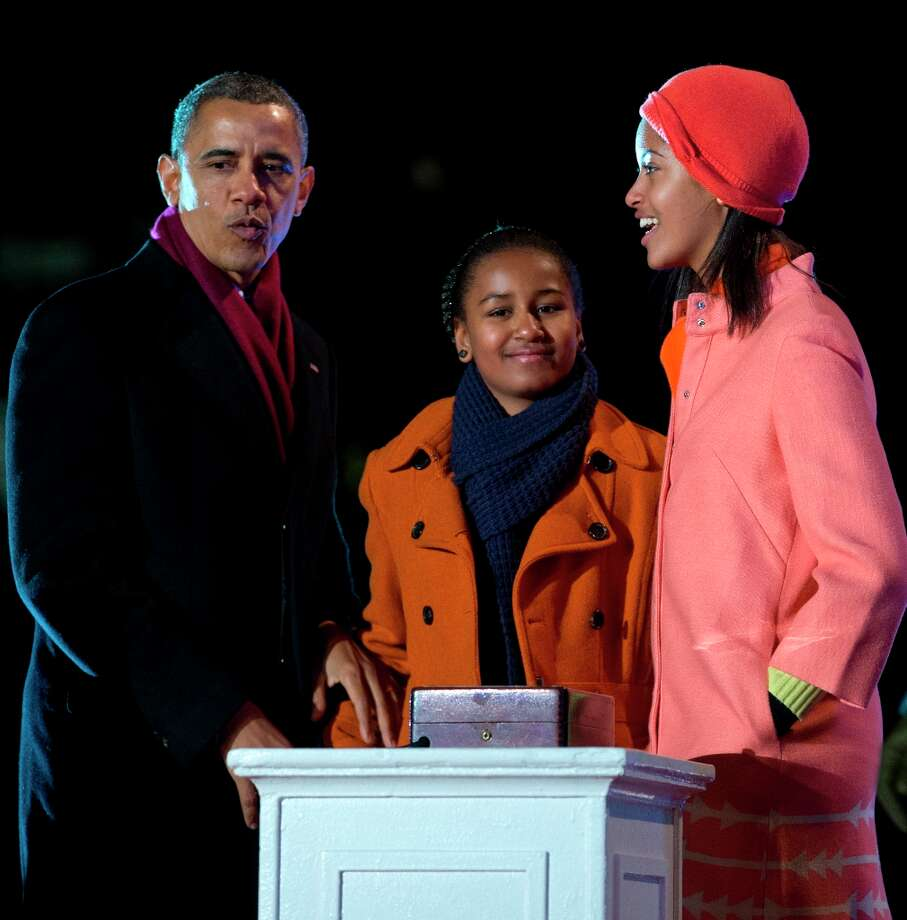 President Barack Obama with his daughters Sasha, center, and Malia, right, react after flipping the switch to light the National Christmas Tree during the annual National Christmas Tree Lighting on the Ellipse, Thursday, Dec. 6, 2012, in Washington. This year's giant blue spruce is new, transplanted in October on the Ellipse, south of the White House. (Carolyn Kaster / AP Photo) Photo: Carolyn Kaster, Associated Press / AP
