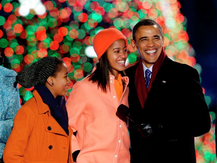 President Barack Obama, right, Sasha Obama, left, and Malia Obama, sing during the 90th annual National Christmas Tree Lighting ceremony on the Ellipse south of the White House, Thursday, Dec. 6, 2012, in Washington. (Alex Brandon / AP Photo) Photo: Alex Brandon, Associated Press / AP