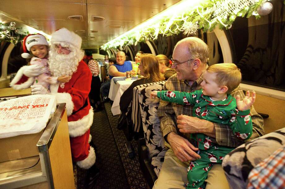 """Austin Townsend, 2, and his grandfather, Joe Dueitt, both of Monroe, La., wait for Santa to visit them as they ride the Polar Express. More than 40,000 people took the trip to the """"North Pole"""" from Palestine last year. Below right, the Palestine Depot welcomes visitors with holiday lights. Photo: Nick De La Torre, Staff / © 2012  Houston Chronicle"""