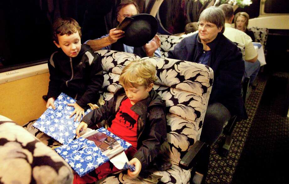 Brady Cates, 6, left, and his brother Jonas Akin, 5, open presents before the Polar Express departs, Friday, Nov. 30, 2012, in Palestine. The boys got copies of the book the Polar Express. The Express will run on weekends untill December 29th. More information at https://www.texasstaterr.com/polar/.  ( Nick de la Torre / Houston Chronicle ) Photo: Nick De La Torre, Staff / © 2012  Houston Chronicle