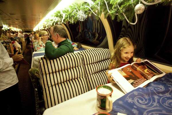 Katharine Koonce, 8, of Houston, follows along with her copy of the Polar Express as she rides the Texas State Raiload's Polar Express ride, Friday, Nov. 30, 2012, in Palestine. The Express will run on weekends untill December 29th. More information at https://www.texasstaterr.com/polar/. ( Nick de la Torre / Houston Chronicle )
