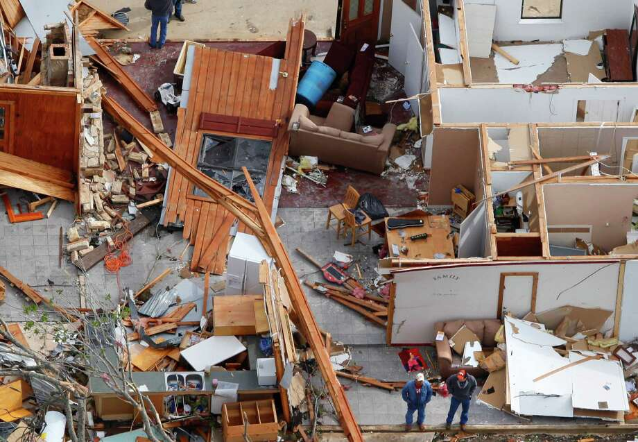 This Tuesday March 20, 2012 aerial picture shows two men, seen in the bottom of the image, as they stand in the remains of a house damaged from an overnight tornado in the Devine area. Photo: William Luther, San Antonio Express-News / © 2012 WILLIAM LUTHER