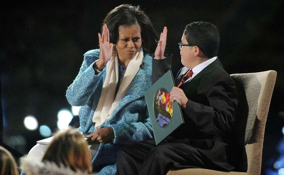 First lady Michelle Obama and Rico Rodriguez, actor on Modern Family read a story to kids during the 90th National Christmas Tree Lighting Ceremony on the Ellipse behind the White House on December 6, 2012 in Washington, DC. This year is the 90th annual National Christmas Tree Lighting Ceremony. Photo: Pool, Getty Images / 2012 Getty Images