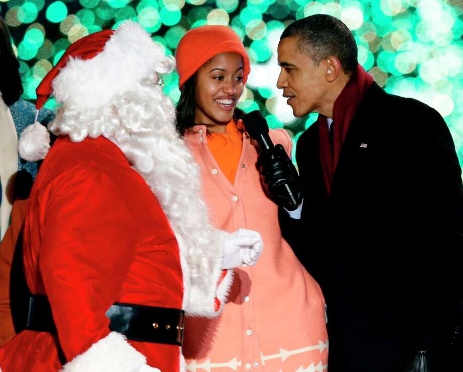 President Barack Obama, right, and daughter Malia Obama, sing as Santa Claus arrives during the 90th annual National Christmas Tree Lighting ceremony on the Ellipse south of the White House, Thursday, Dec. 6, 2012, in Washington. (Alex Brandon / AP Photo) Photo: Alex Brandon, Associated Press / AP