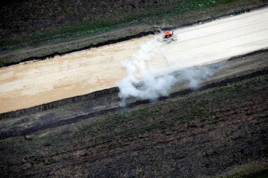 A street sweeper clears debris from the still-under-construction State Highway 130 between Lockhart and Seguin, Texas as seen in this Thursday afternoon July 26, 2012 aerial photos. The road opened in late October. Also called Toll 130, it runs from Seguin, parallel to I-35, all the way to Georgetown and will be the closest toll road to San Antonio. Photo: William Luther, San Antonio Express-News / © 2012 San Antonio Express-News