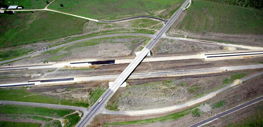 A smaller road crosses over the still-under-construction State Highway 130 between Lockhart and Seguin, Texas in this Thursday afternoon July 26, 2012 aerial photo. The road opened in late October. Also called Toll 130, it runs from Seguin, parallel to I-35, all the way to Georgetown and will be the closest toll road to San Antonio. Photo: William Luther, San Antonio Express-News / © 2012 San Antonio Express-News