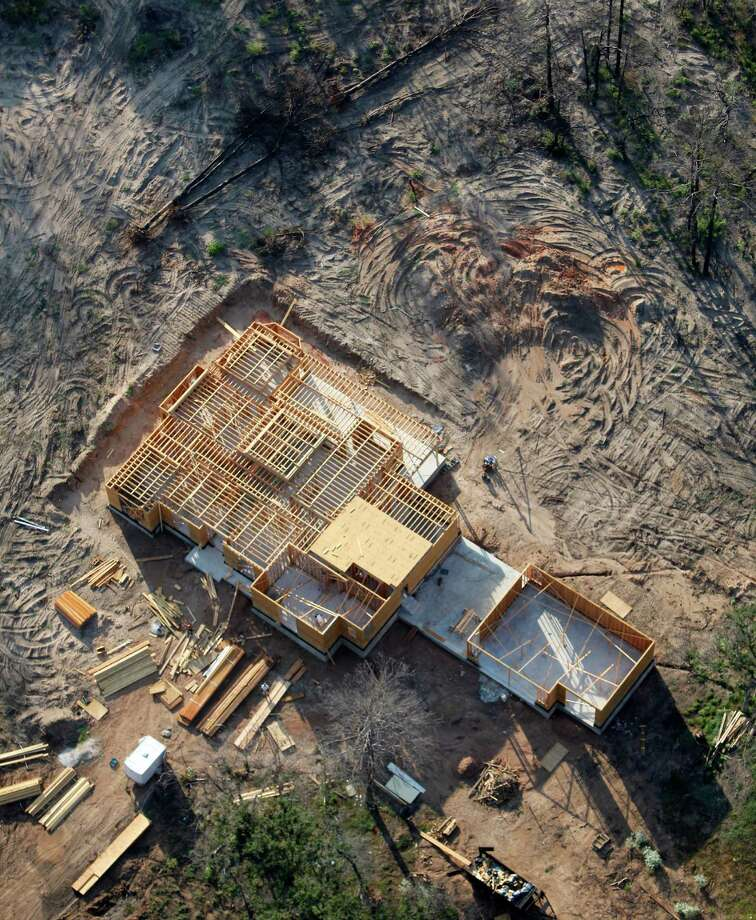 As the one-year anniversary of the The Bastrop Fire Complex fire that burned much of Bastrop State Park and the so-called Lost Pines area of central Texas approaches, a still-under-construction replacement home for a house destroyed by the fire is seen in a Monday Aug 20, 2012 aerial image. Photo: William Luther, San Antonio Express-News / © 2012 San Antonio Express-News