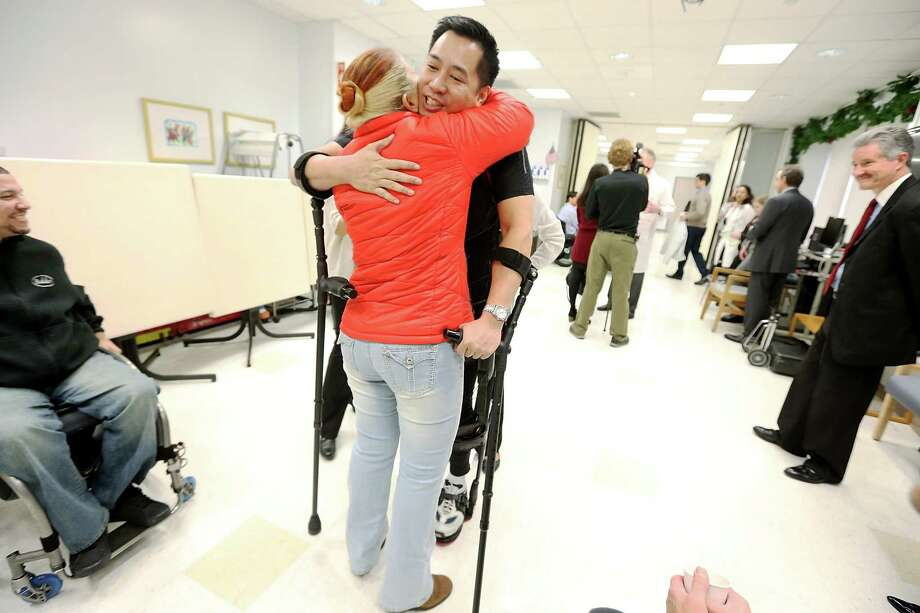 NEW YORK, NY - DECEMBER 06:  Forty three-year-old parapalegic Robert Woo hugs Deborah Kuryz while walking with an exoskeleton device made by Ekso Bionics during a demonstration at the opening of the Rehabilitation Bionics Program at Mount Sinai Rehabilitation Center on December 6, 2012 in New York City. Woo is an architect who was paralyzed from the hips down during a construction accident and thought he would never walk again. The new strap-on exoskelton uses motors and sensors to physically move the legs. Photo: Mario Tama, Getty Images / 2012 Getty Images