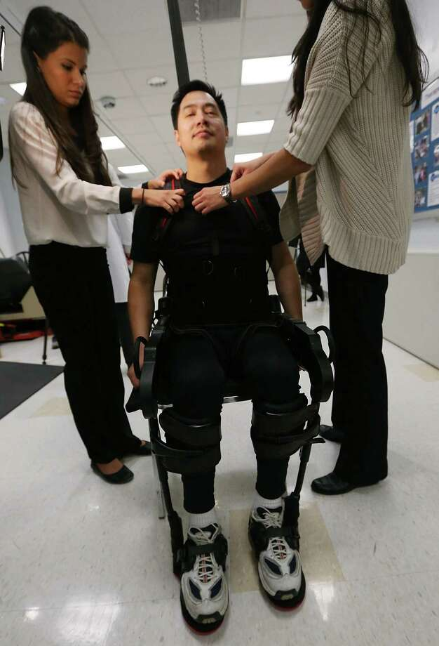 NEW YORK, NY - DECEMBER 06:  Forty three-year-old parapalegic Robert Woo is outfitted with an exoskeleton device to walk in made by Ekso Bionics as Manuel Maldonado (L) during a demonstration at the opening of the Rehabilitation Bionics Program at Mount Sinai Rehabilitation Center on December 6, 2012 in New York City. Woo is an architect who was paralyzed from the hips down during a construction accident and thought he would never walk again. The new strap-on exoskelton uses motors and sensors to physically move the legs. Photo: Mario Tama, Getty Images / 2012 Getty Images