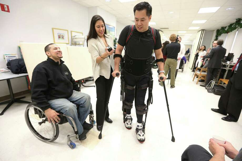 NEW YORK, NY - DECEMBER 06:  Forty three-year-old parapalegic Robert Woo walks with an exoskeleton device made by Ekso Bionics as Manuel Maldonado (L) looks on during a demonstration at the opening of the Rehabilitation Bionics Program at Mount Sinai Rehabilitation Center on December 6, 2012 in New York City. Woo is an architect who was paralyzed from the hips down during a construction accident and thought he would never walk again. The new strap-on exoskelton uses motors and sensors to physically move the legs. Photo: Mario Tama, Getty Images / 2012 Getty Images