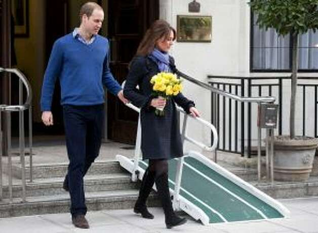 FILE- In this Thursday, Dec. 6, 2012 file photo, Britain's Prince William stand next to his wife Kate, Duchess of Cambridge as she leaves the King Edward VII hospital in central London. Prince William and his wife Kate are expecting their first child, and the Duchess of Cambridge was admitted to hospital suffering from a severe form of morning sickness in the early stages of her pregnancy. King Edward VII hospital says a nurse involved in a prank telephone call to elicit information about the Duchess of Cambridge has died. The hospital said Friday, Dec. 7, 2012 that Jacintha Saldanha had been a victim of the call made by two Australian radio disc jockeys. They did not immediately say what role she played in the call. Photo: AP