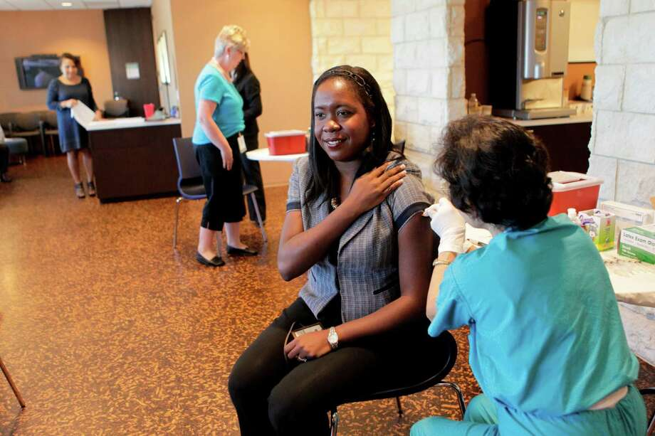 Abby Spring-Mann gets a flu shot by registered nurse Helen Wu, of Memorial Hermann, in this 2010 photo. Photo: Julio Cortez, Staff / Houston Chronicle