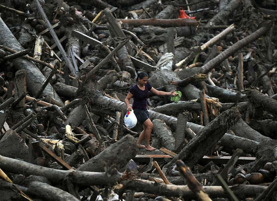 A resident carrying a bag full of relief goods walks through debris to her home in New Bataan in the Philippines' Compostela Valley province. More than 500 people remain missing. Photo: Ted Aljibe, AFP/Getty Images