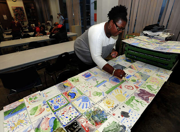 Michelle Crayton puts the finishing touches on a tile art piece during a Christmas event at the Art Museum of Southeast Texas on Thursday. The tiles will be part of the All Access Playground to be constructed near the Town Lake Event Centre.  Photo taken Thursday, December 06, 2012 Guiseppe Barranco/The Enterprise Photo: Guiseppe Barranco, STAFF PHOTOGRAPHER / The Beaumont Enterprise