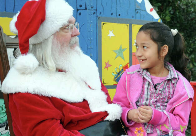 Yabhira Artega, 8, poses with Santa for a photo during a Christmas event at the Art Museum of Southeast Texas on Thursday.  Photo taken Thursday, December 06, 2012 Guiseppe Barranco/The Enterprise Photo: Guiseppe Barranco, STAFF PHOTOGRAPHER / The Beaumont Enterprise